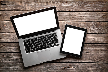 tablet: Open laptop with digital tablet. With isolated screen on old wooden desk. Stock Photo