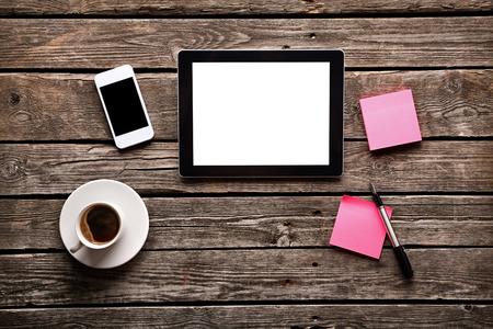 Digitální tablet počítač s lepkavou dopisní papír a šálek kávy na starém dřevěném stole. Jednoduchá pracovní prostor nebo přestávka na kávu s surfování po webu.