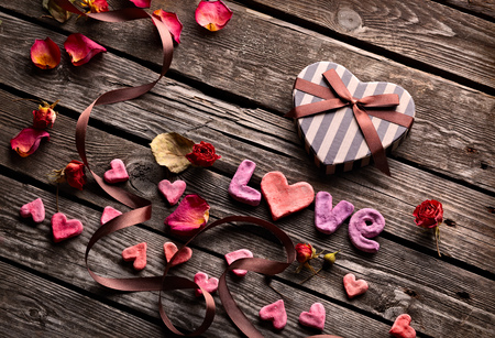 heart shaped stuff: Word Love with Heart shaped Valentines Day gift box on old vintage wooden plates. Sweet holiday background with rose petals, small hearts, curved ribbon. Stock Photo