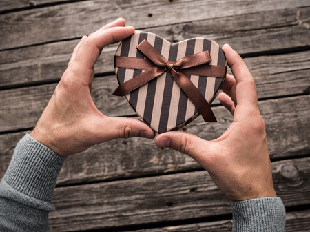mirth: Heart shaped gift box in mans hands. Top view.