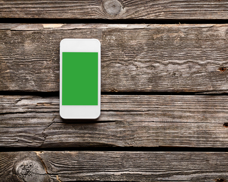 phone isolated: White smart phone with isolated screen on old wooden desk.