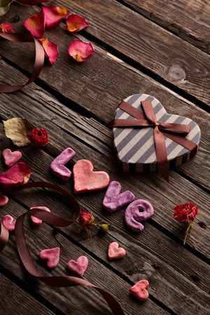 heart shaped stuff: Word Love with Heart shaped Valentines Day gift box on old vintage wooden plates. Stock Photo