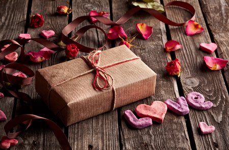 curved ribbon: Word Love with gift box on old vintage wooden plates. Sweet holiday background - rose petals, small hearts, curved ribbon, etc.