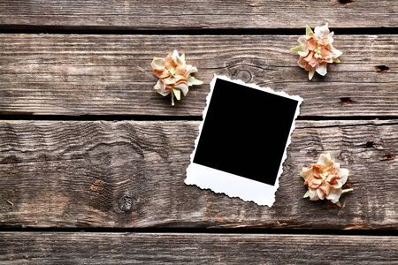 dried flowers: Blank instant photo frame with dried flowers on old wooden background. Stock Photo