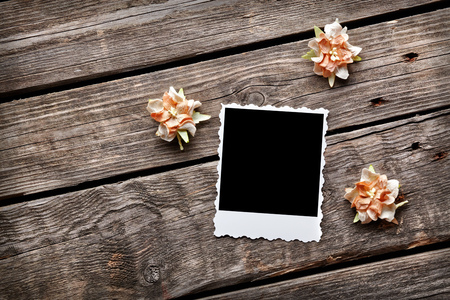 flores secas: Blank instant photo frame with dried flowers on old wooden background. Foto de archivo
