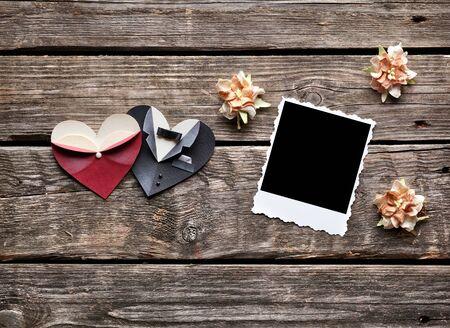 flores secas: marco de foto instant�nea con flores secas y masculina simb�lica y el coraz�n formas femeninas en el fondo de madera vieja. Foto de archivo