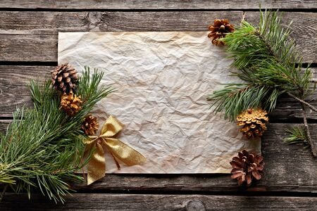 spruce: Old crumpled paper with spruce twigs and golden bow. Sweet Xmas holiday background.