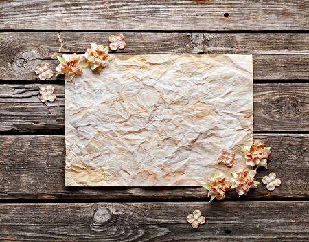 wood craft: Old crumpled paper with dried flowers or craft flowers on old wood. Sweet holiday background.