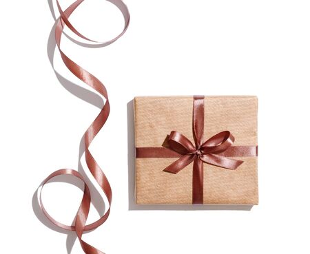 Craft gift box with curved brown ribbon isolated on white background.