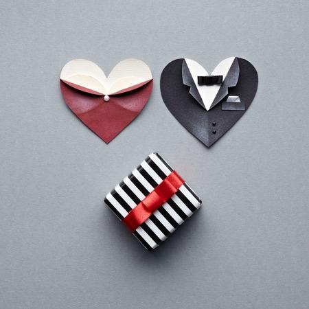 corazón formas femeninas con caja de regalo masculina simbólica y. Sobre fondo gris. Boda o tema st.Valentine. Foto de archivo