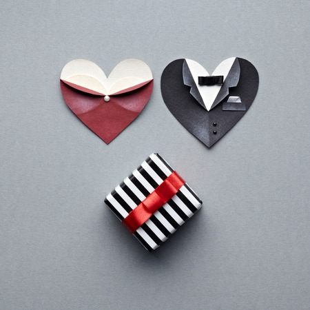 paper heart: Symbolic male and female heart shapes with gift box. On gray background. Wedding or st.Valentine theme.