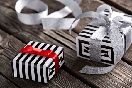 silver ribbon: Gift boxes with curved silver ribbon on old wooden background.