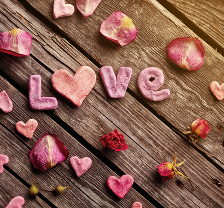heart shaped stuff: Word Love with rose petals and small heart shaped stuff on old vintage wood plates. Sweet holiday background.