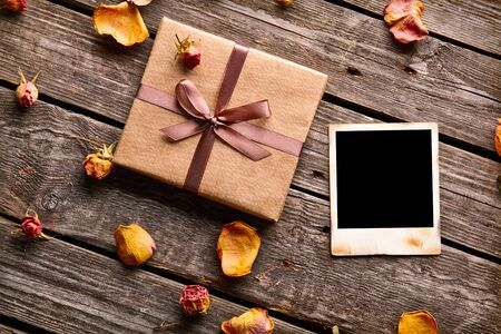 frame  box: Blank photo frame with gift box, petals and rose flowers on old wooden background. Stock Photo
