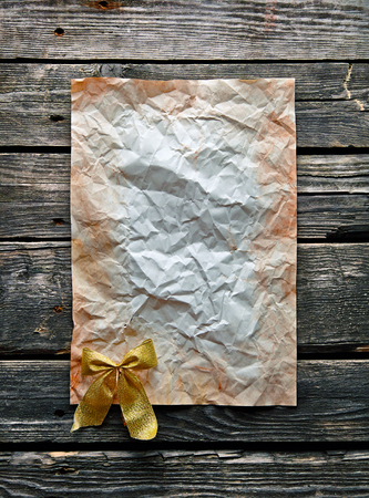 crumpled sheet: Crumpled sheet of paper with gold bow on old wood. With space for text.