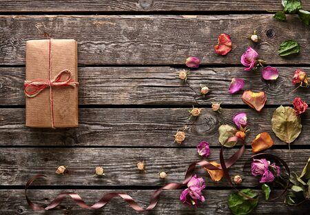 flores secas: caja de regalo de la tecnología de pétalos de rosa y flores secas en antiguos platos de madera. fondo precioso vacaciones.