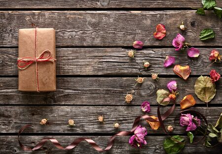 dried flowers: Craft gift box with rose petals and dried flowers on old wooden plates. Lovely holiday background. Stock Photo