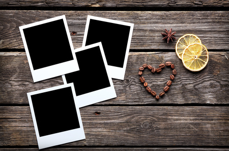 vintage photo: Four blank instant photo frames with coffee beans in shape of a heart on old wooden background.