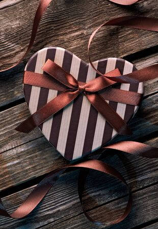 curved ribbon: Heart shaped Valentines Day gift box with curved ribbon on old wood. Vintage holiday background. Stock Photo