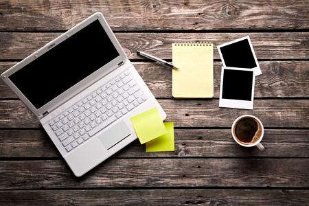 hacer: Ordenador portátil con la taza de café, fotos instantáneas y papel nota adhesiva con la libreta en la tabla de madera