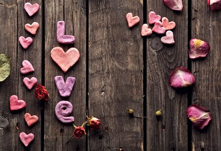 flower shape: Word Love with rose petals and small heart shaped stuff on old vintage wood plates. Sweet holiday background.