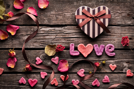Word Love with Heart shaped Valentines Day gift box on old vintage wooden plates. Sweet holiday background with rose petals, small hearts, curved ribbon. Archivio Fotografico