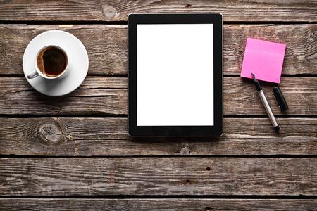 taza cafe: Ordenador tableta digital con papel de nota adhesiva y una taza de café en la mesa de madera vieja. Área de trabajo o simple pausa para el café con la navegación web.