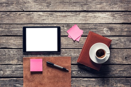 Digital tablet computer with sticky notes and coffee cup on wooden desk. Clipping path included.