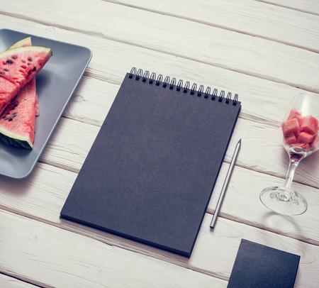 sketchbook: Black sketchbook on kitchen table with sliced watermelon around