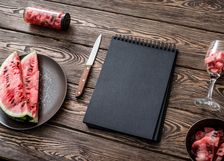 carte: Black sketchbook on kitchen table with sliced watermelon around