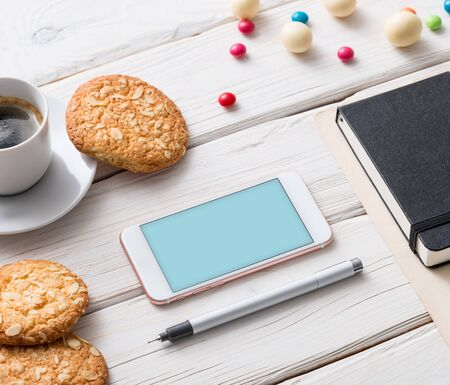 kitchen device: White smart phone on a cafe desktop among cookies with coffee cup. Clipping path included.