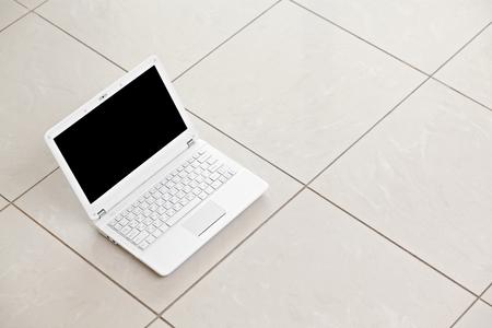 tiled floor: White laptop on bright tiled floor background Stock Photo