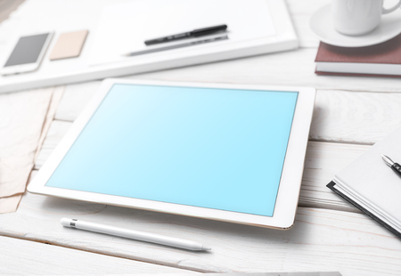 Tablet device mockup with stylus and office supplies on the office desk. Clipping path included.