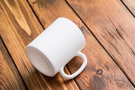 mug: White cup laying in the center of wooden table