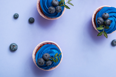 Tasty cupcakes with blue cream over plain background. Top view. Stock Photo