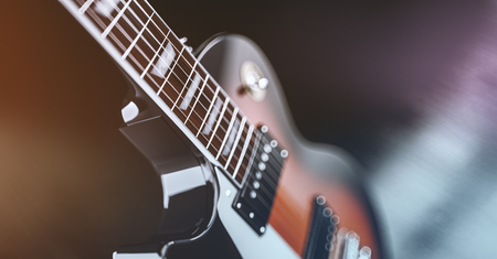 Close up shot of a guitar, over blured lights background Stock Photo
