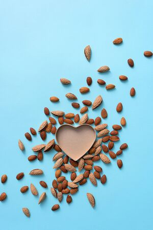 Heart shaped gift box among almonds