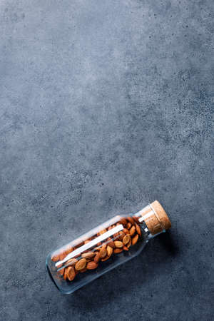 Almond nuts in corked glass jar on a concrete desktop Banque d'images