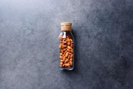 Almond nuts in corked glass jar on a concrete desktop Фото со стока