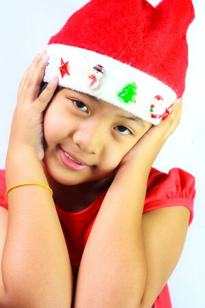 Girl wearing red Santa hats, smiling and hands are raised to her ears photo