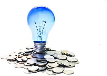 ahorro energetico: l�mpara en las monedas Foto de archivo