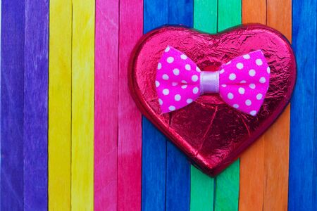 red heart shape on colorful wood background photo