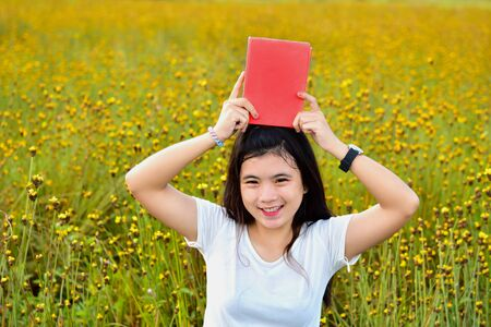 Cute Asian girl holds red book on head. In the middle of a yellow flower field, thoughts, love, reading and education. Stock Photo