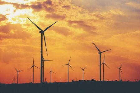 De zon staat achter de windturbine die wordt gebruikt om elektriciteit op te wekken. Hernieuwbare energieconcepten en de wereld helpen energie te besparen Stockfoto