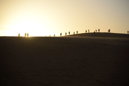 Group of people on top of sand dune watching the setting sun  photo