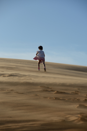 conquer adversity: Young girl walking up a sand dune in the desert
