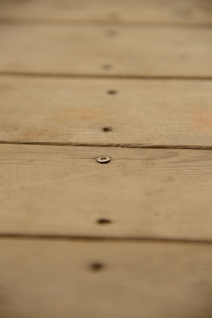Line of screw holes in old and weathered planks of wood   Only one screw remaining Stock Photo - 22901185