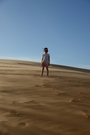 Young girl standing in the desert while getting blasted by the wind  Stock Photo