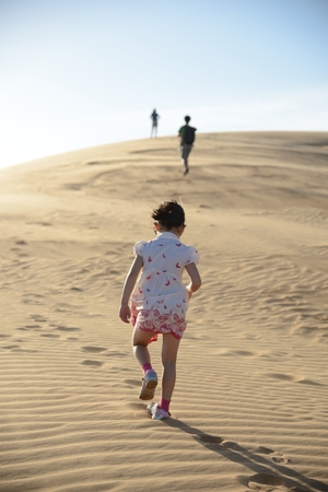 Young girl in white dress walking  in the footsteps of her father and other family members across a large sand dune in the desert