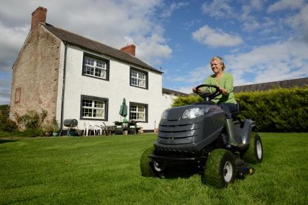 farm house: Senior lady cutting lawn of country farm house Stock Photo